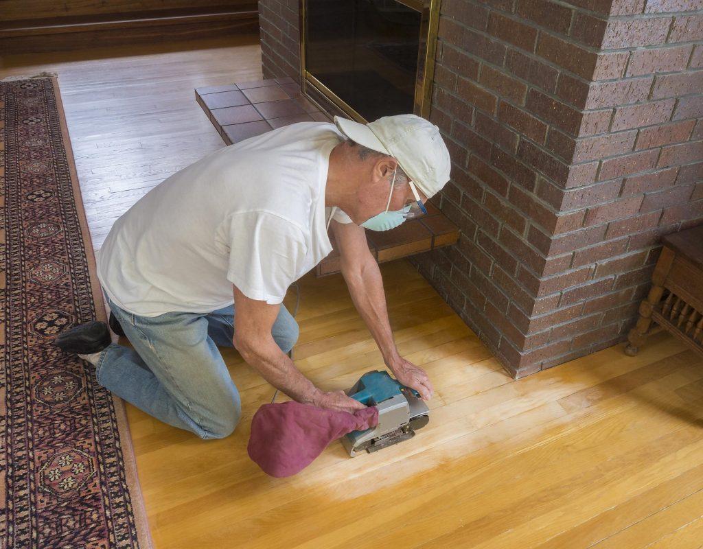 man sanding the wood flooring