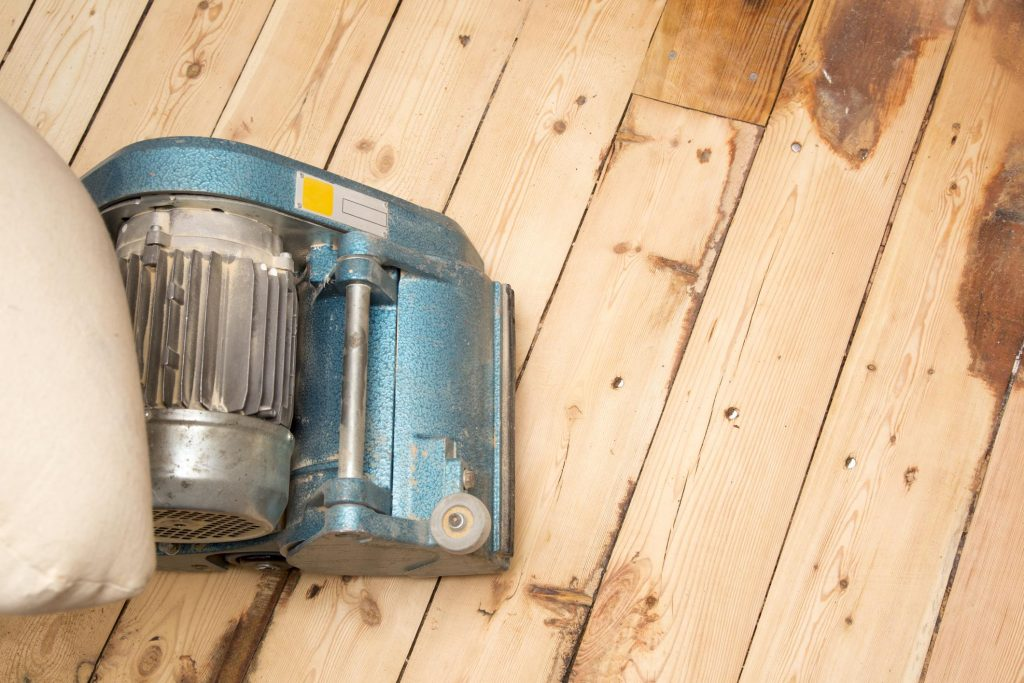 a sanding machine on the wood flooring