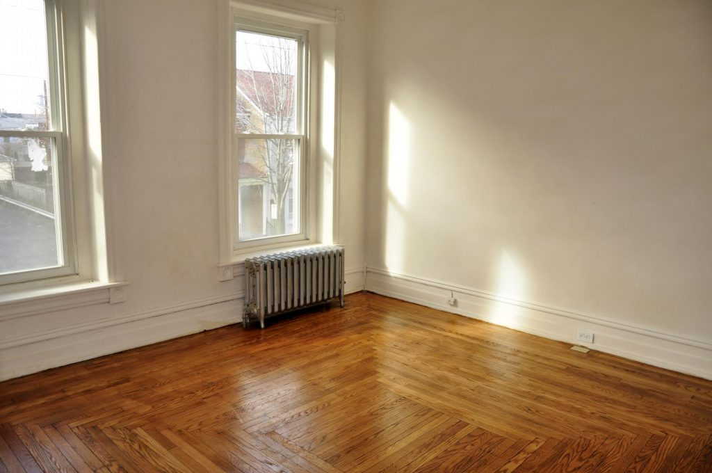 a room with wood flooring and white wall